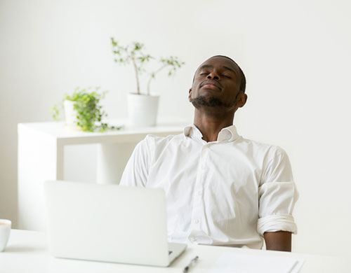 man at desk taking a time out from working